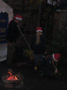 Pfadfinder von Sirius am Lagerfeuer auf dem Weihnachtsmarkt in Köln Brück